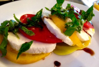 Caprese salad with red and yellow heirloom tomatoes